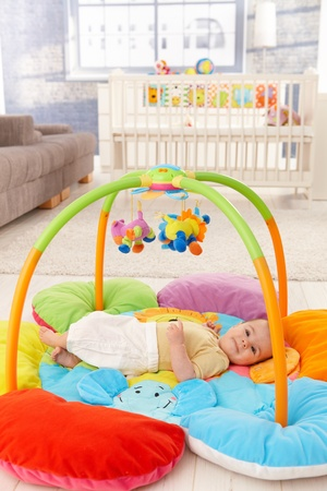 playmat: Happy baby girl smiling on playmat. Stock Photo