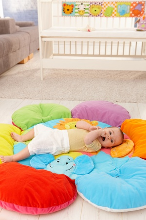 Content baby lying on flowery playmat, with hands in mouth. photo