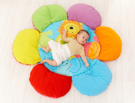 high angles: Baby lying on flower shape playmat, high angle. Stock Photo