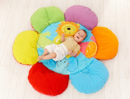 playmat: Happy baby lying on colorful flower playmat, smiling, elevated view. Stock Photo