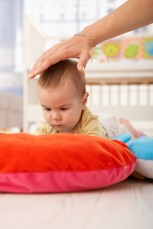 Baby on playmat concentrating, mother holding hand to protect infant. photo