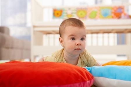 Cute infant crawling on playmat. photo