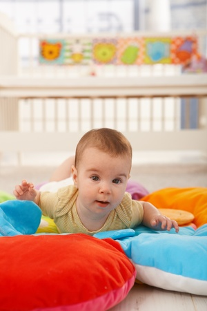 playmat: Sweet baby crawling on colorful playmat. Stock Photo