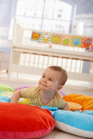 copy room: Happy cute infant lying on playmat, trying to crawl.