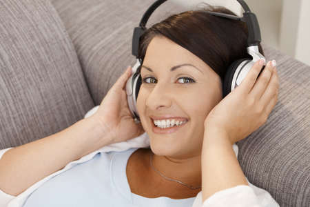 Happy young woman listening music on headphones, lying on sofa at home, smiling. photo