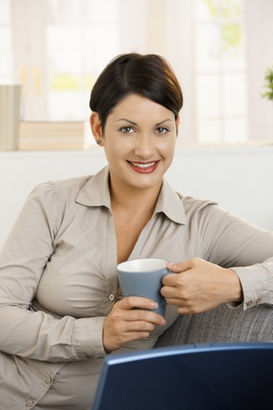Closeup portrait of happy young woman drinking tea at home, smiling. photo