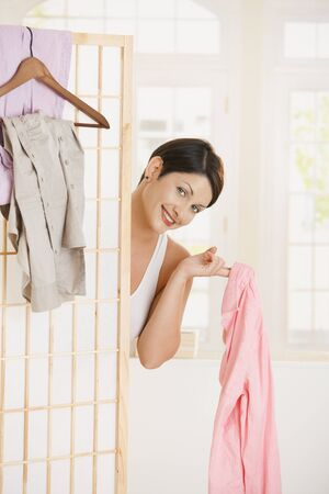 Sexy young woman undressing, looking out beckoning behind dressing panel, showing up pink shirt. photo