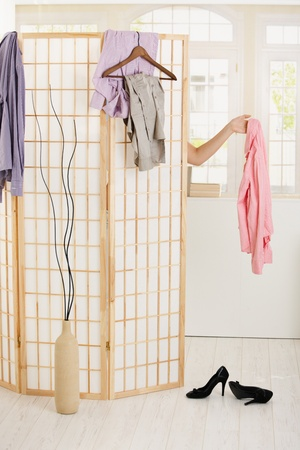 women undressing: Woman undressing behind dressing panel, holding out pink shirt. Stock Photo