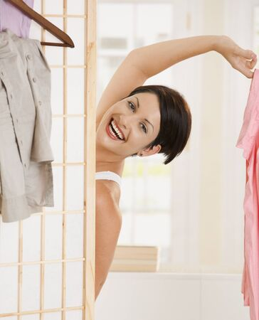 looking behind: Happy young woman undressing, looking out beckoning behind dressing panel, holding pink shirt. Stock Photo