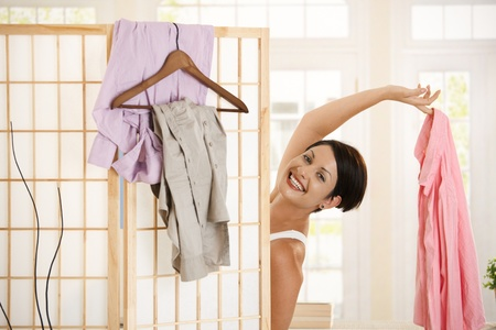 Happy young woman dressing up, looking out behind dressing panel, showing up pink shirt. photo