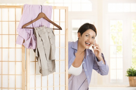 Happy young woman talking on mobile looking out behind dressing panel, smiling. photo