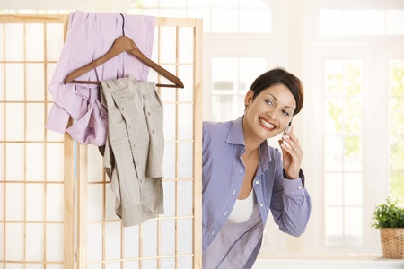 Happy young woman talking on mobile phone while dressing up in the morning, smiling. Stock Photo - 8747570