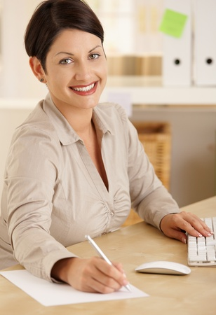 Happy office worker working at desk writing notes. Looking at camera, smiling. photo