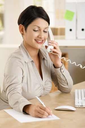 Young businesswoman working at home, talking on phone, writing notes. photo