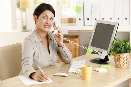 Office worker sitting at desk in office, talking on phone, taking notes, smiling.