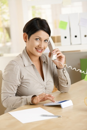 Young businesswoman working at home, talking on phone, using calculator. photo