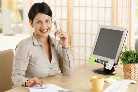 Happy businesswoman working at desk in office, talking on phone, using calculator. Copyspace on screen. photo