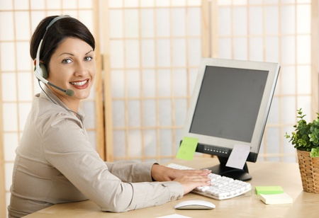 looking at computer screen: Young woman working at home, talking on headset, using computer. Copyspace on blank screen.