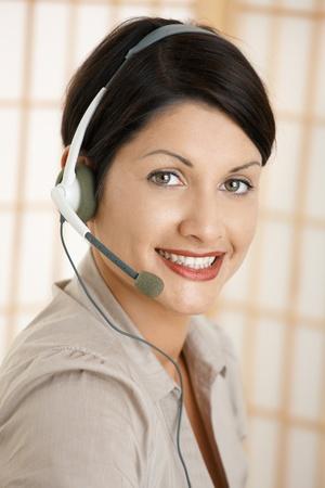 Closeup portrait of attractive customer service operator talking on headset. photo