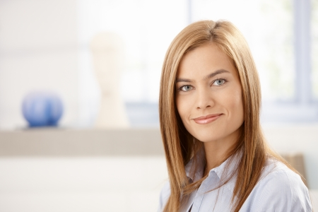 Portrait of attractive young woman smiling front of window. photo