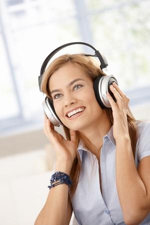 Attractive girl listening music through headphones, smiling. photo