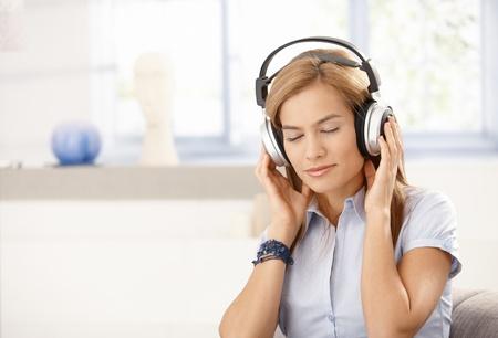 Young female enjoying music through headphones, eyes closed. photo