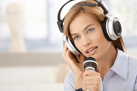 Attractive young woman singing with microphone, wearing headphones. photo