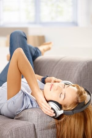 Young attractive woman listening music through headphones, laying on sofa. photo