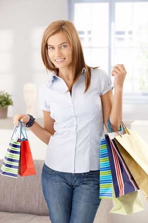 Young attractive woman standing in living room with shopping bags, smiling. photo