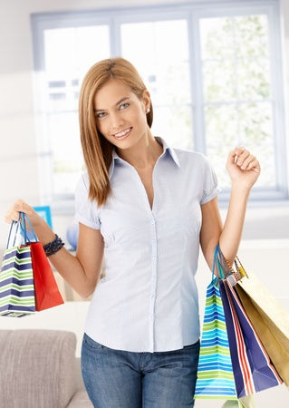 Attractive girl arriving from shopping with shopping bags, smiling happily. photo