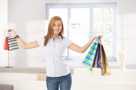 outspreading: Attractive girl holding shopping bags in hands, smiling happily at home.