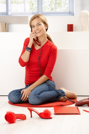Pretty girl in red pullover talking on phone, sitting on floor at home, smiling. photo