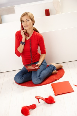 Young attractive female sitting on floor in red pullover, talking on phone, smiling. photo