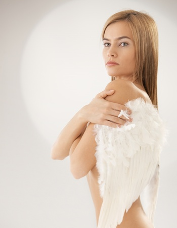 Attractive woman standing half nude, wearing angel wings, side view. photo