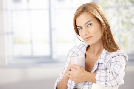 Morning portrait of attractive young girl wearing pyjama, drinking coffee. photo