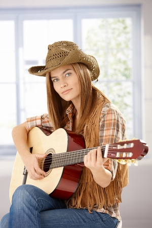 Attractive young girl playing guitar in western hat. photo