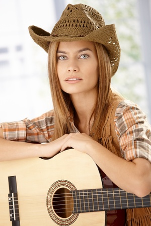 western european: Portrait of attractive girl with guitar and western hat. Stock Photo