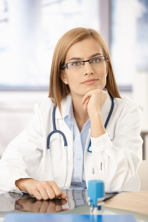Young medical student sitting at desk in office, smiling, wearing glasses.