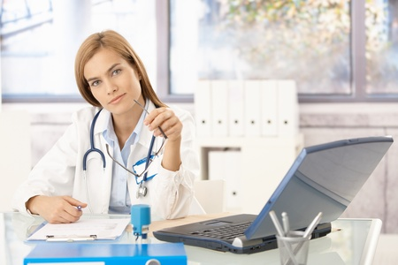 consultant physicians: Attractive female doctor sitting at desk in office writing report, smiling. Stock Photo