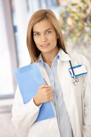 Young attractive female doctor standing front of window, holding papers, smiling. photo