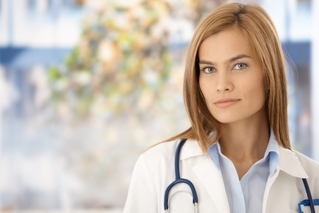 Portrait of young attractive female doctor in hospital, standing front of window. photo