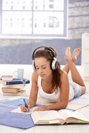 Attractive girl learning at home laying on floor, using headphones. Stock Photo - 8747503