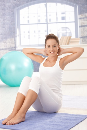 Attractive young female doing exercises on floor at home, smiling. photo