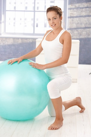 Pretty young girl exercising with fitball at home, smiling. Stock Photo - 8747477