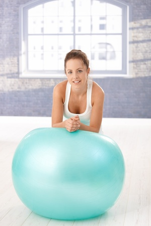 Attractive young woman resting on fitball after workout, smiling in gym. Stock Photo - 8747474