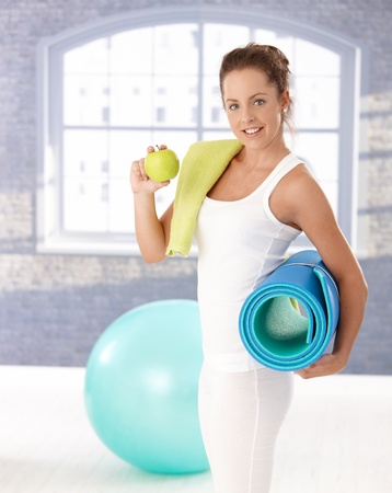 look after: Attractive young female having an apple after workout in gym. Stock Photo