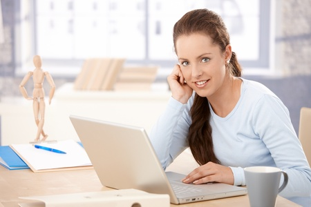 sadece kadınlar: Attractive young woman working on laptop in bright office, smiling.