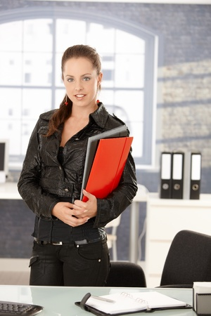 Young attractive woman working in bright office, standing by desk, holding folders smiling. photo