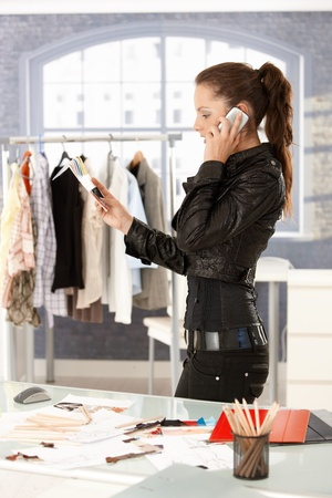 Young attractive fashion designer talking on phone by desk in office, working. photo