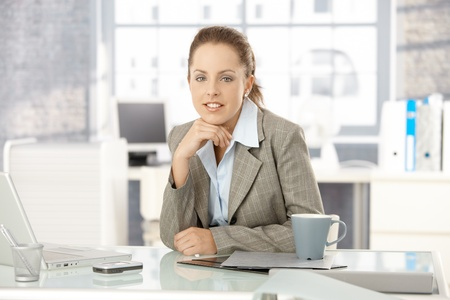 Young attractive businesswoman sitting by desk in office, having laptop. photo